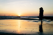Silhouette Of An Anonymous Girl Walking In The Beach During The Sunset