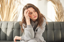 Unnerved Girl Holding Her Head, Woman Has A Headache. Sad Female Sitting On Couch