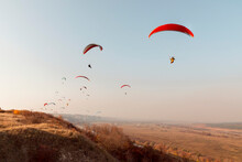 Paragliders Fly In Autumn Over Hills
