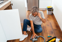 Adult Man Calling The Repair Service At Home