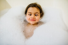 Young Girl Making Silly Face Laying In A Bubble Bath.
