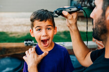 Young Boy With A Goofy Face Getting His Hair Cut.