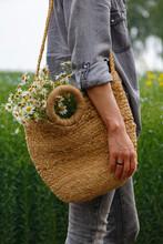 Crop Woman With Basket Of Flowers Walking In Meadow