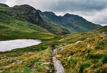 Female Walking Past Red Tarn On Route To Pike Of Blisco. Lake District, Cumbria, UK.
