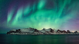 Blue and green glowing northern lights over norwegian winter landscape