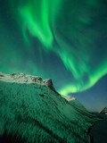 Strong northern lights over snow covered mountains in Norway.