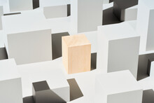 Wooden Cube Amidst Geometric Shapes