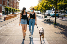 Girlfriends In Masks Walking With Dog