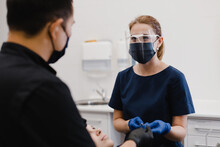 Female Assistant Talking With Dentist During Appointment