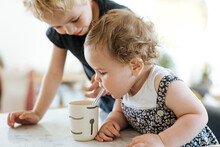 Brother Helping Sister Drink From Cup With Plastic Straw