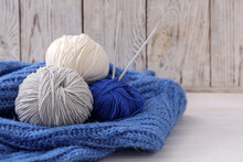 Soft Woolen Yarns With Knitting Needles And Sweater On White Table, Closeup. Space For Text