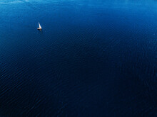 Tiny Sailboat In The Sea