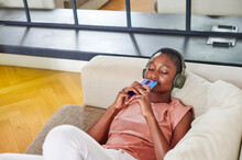 Woman Relaxing To Music On Her Sofa