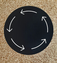 Black Circle With White Arrows On Stone Floor