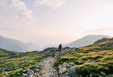 Female Walker At Sunrise Climbing Up To Scafell Pike From Wasdale.