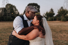 Bride And Groom In Intimate Hug On Wedding Day At Sunset