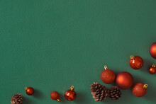 Row Of Red Christmas Ball Decorations And Pine Cones On A Green Background