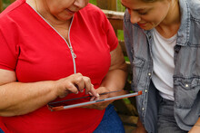 Crop Women Browsing Tablet Together