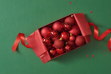 Red Christmas Filled Box With Red Christmas Decoration On Green Background. Open Christmas Box With Christmas Ball Inside
