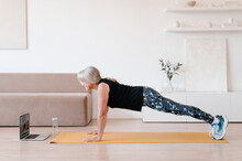 Elderly Sportswoman Doing Plank Exercise During Online Workout