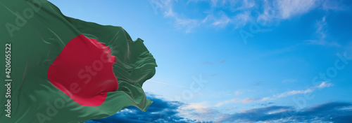 Fotografie, Tablou Large flag of Bangladesh  waving in the wind on flagpole against the sky with clouds on sunny day