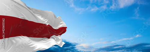 Fototapeta Large flag of belarus  waving in the wind on flagpole against the sky with clouds on sunny day. 3d illustration obraz