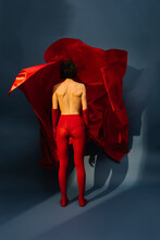 Woman Playing With Red Silk Fabric On Blu Background
