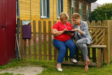 Daughter Teaching Mother To Use Tablet Near Fence