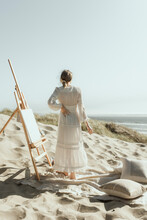 Young Woman Painting On An Easel At The Coast In The Sand