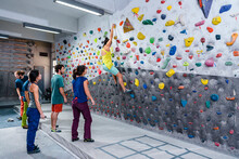 Sporty Friends With Instructor Practicing Climbing Wall