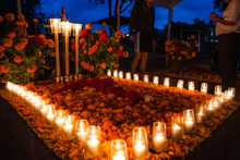 Marigolds And Candles Adorn A Community Graveyard At Night