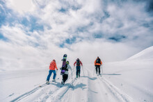 Group Of Friends Hiking Up A Mount Hekla In Iceland With Skis An