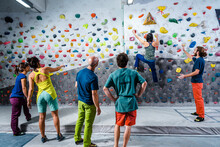 Active Friends With Instructor Practicing Climbing Wall
