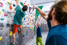 Sporty Male Climbing Indoor Wall During Workout