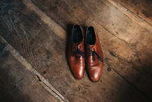 Brown Leather Men Shoes On A Very Old Dark Wooden Floor