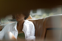 Black Woman Sitting In The Back Of A White Vintage Car