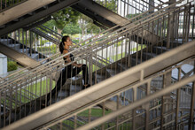 Asian Woman Exercising Outdoors Stretching On A Steel Staircase