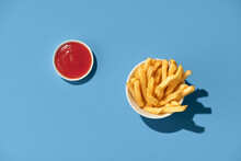 French Fries With Ketchup On Blue Background.