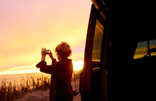 Wanderlust Woman Taking A Picture Of The Sunset On A Roadtrip Through California