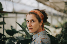 A Beautiful Curly Woman In A Green House