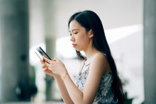 Young Asian Women Using Mobile Phones On The Street In The City