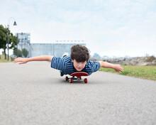Boy Riding Skateboard Outside On Road