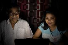 Teenage Girl Enjoying Movie In Laptop With Grandfather