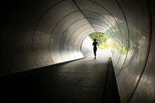 The Silhouette Of A Runner As She Passes Through A Tunnel In Singapore.