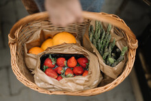 Close Up Of A Woman Holding A Basket Full Of Fresh Vegetables And Fruits