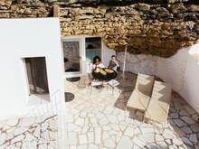 Couple Having Breakfast In Yard Of Stylish Stone House