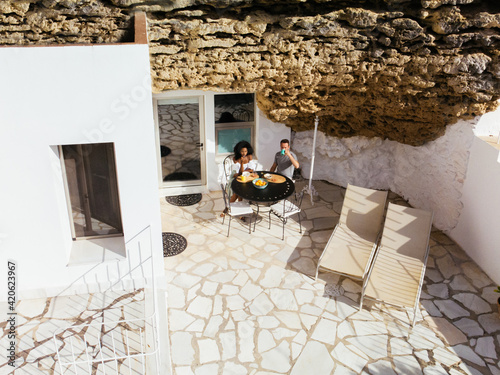 Couple having breakfast in yard of stylish stone house