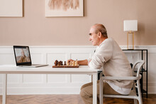 Senior Man Playing Chess With Online Partner