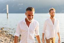 Happy Homosexual Couple Walking Along The Beach
