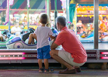 Grandfather With His Grandson Watching A Fairground Ride
